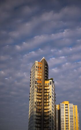 High-rise buildings structural geometric exterior and glass and metal balconies reflection the sun in the last rays of the sun against a cloudy sky
