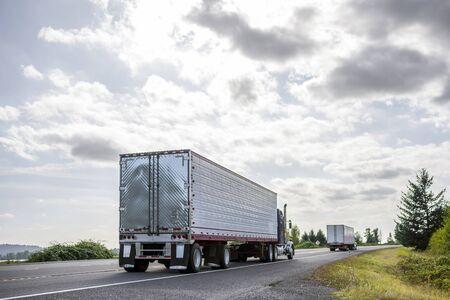 Oude klassieke Amerikaanse motorkap blauwe grote rig semi-vrachtwagen met verticale uitlaatpijpen die bevroren voedsel vervoeren in een koelkast oplegger die op de pittoreske weg in het Columbia Gorge-gebied loopt Stockfoto