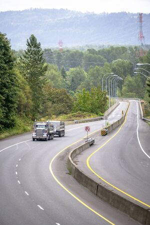 Big rig classic powerful tip truck with two dump semi trailers driving on winding divided highway road with concrete separation barrier and lantern and green forest trees in Columbia Gorge