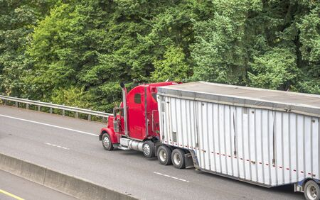 Bright red classic big rig semi truck with vertical pipes transporting industrial cargo in covered corrugated bulk semi trailer running on the turning road with green trees on the side Stock Photo