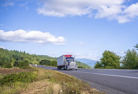 Old Classic American bonnet blue big rig semi truck with vertical exhaust pipes transporting frozen food in refrigerator semi trailer running on the picturesque road in Columbia Gorge area Stock Photo