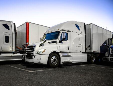 Diferentes marcas y modelos de camiones grandes con semirremolques parados en el estacionamiento de la parada de camiones debajo del refugio iluminado por la noche y cumplir con el movimiento de acuerdo con el horario.