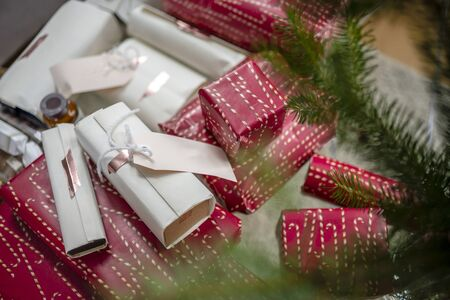 Bright Christmas decorations and gift boxes in holiday wrappers with tags and ribbon folded under the Christmas tree for fun and pleasure Xmas celebration of the whole family together Banco de Imagens
