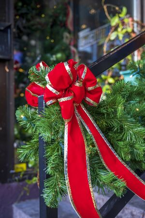 Original Christmas decorations from Christmas tree branches with a woven garland of lights and a red bow on the railing of the home stairs on time of Xmas celebration Events