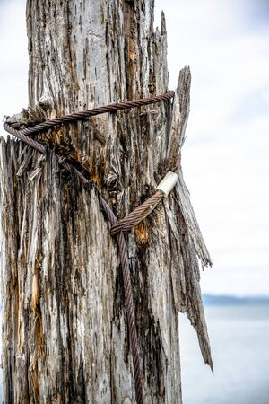 Old rotten pier with rotten loose piles driven into the bottom of the bay and metal rusty ties for a reliable bundle of parts of the pier at the mouth of the Columbia River in the Pacific Ocean Stockfoto