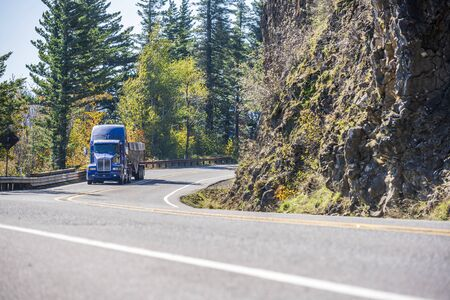 Blue bonnet American powerful big rig semi truck transporting commercial cargo in covered bulk semi trailer turning around the cliff on the winding mountain road with autumn trees in Columbia Gorge