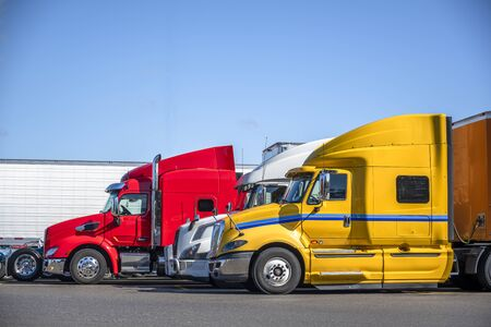 Different makes and colors of big rigs semi trucks with semi trailers standing in row on truck stop parking lot for truck drivers rest and adherence to the transportation schedule