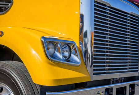 Front part of yellow professional big rig industrial powerful bonnet semi truck with chrome grille and bumper and headlight with reflection of sunlight stand-ing on the parking lit 스톡 콘텐츠