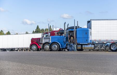 Two Truck drivers exchange views on the strengths and weaknesses of their big rigs semi trucks standing on the truck stop parking lot for night rest and continue the route the next day Stock Photo