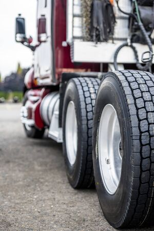 Wheels of big rig dark red commercial powerful bonnet semi truck with embossed tire tread standing on the truck stop parking lot ready to the next delivery according to the approved schedule