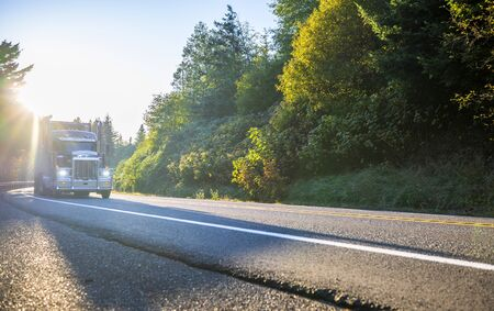 Big rig classic white pro American bonnet semi truck with refrigerator unit transporting frozen cargo in refrigerated semi trailer running on the mountain road with sunlight and autumn trees