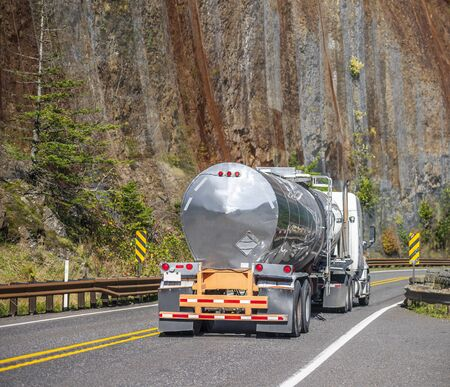 Industrial heavy-duty white big rig semi truck transporting liquid cargo in stainless steel tank semi trailer running uphill on the winding autumn road with rock mountain wall in Columbia Gorge