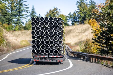 Big rig professional industrial grade transportation semi truck transporting stacked in square plastic pipes on the flat bed semi trailer running on winding road with hills and autumn yellow trees