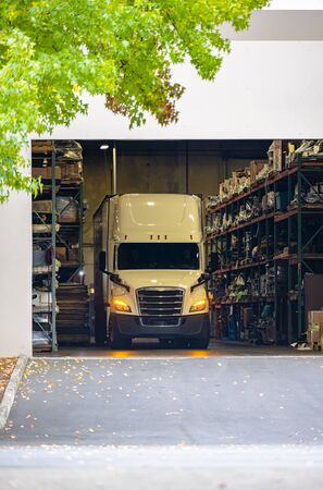 Big rig white bonnet long haul semi truck with turned on headlights and dry van semi trailer standing inside of warehouse with racks and loads for unloading delivered commercial cargo