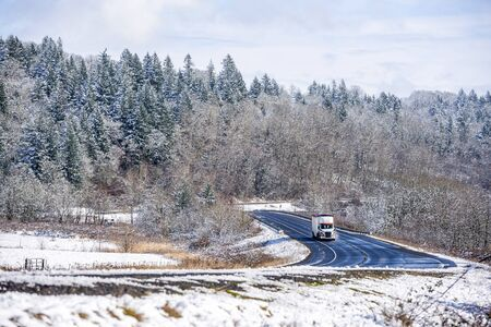 White bonnet popular professional big rig semi truck with bulk semi trailer going on the wet dangerous slippery icy winter road with snow on the trees and the sides of the winding highway