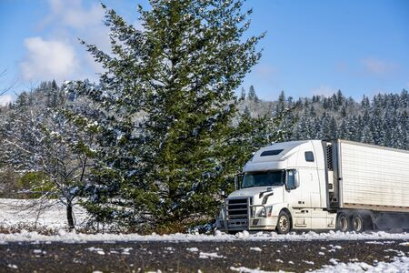 White modern bonnet popular professional big rig semi truck with refrigerator semi trailer going on the wet dangerous slippery icy winter road with snow on the trees on the sides of the highway