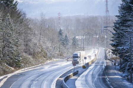 Big rig white long haul semi truck with grille guard transporting commercial goods in dry van semi trailer driving on the turning winter snowy wet dangerous highway with trees on the sides