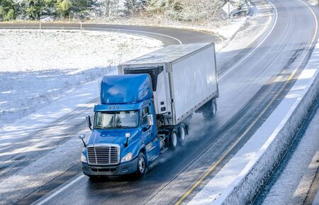 Big rig blue bonnet day cab semi truck with roof spoiler and refrigerator unit on the front wall of reefer semi trailer transporting commercial cargo driving on the turned winter wet road with snow