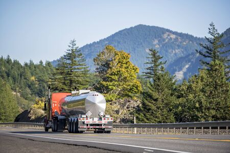 Big rig classic American powerful long haul semi truck transporting liquid cargo in tank semi trailer running on the flat road with autumn trees and sunshine on the side in Columbia Gorge area Banco de Imagens