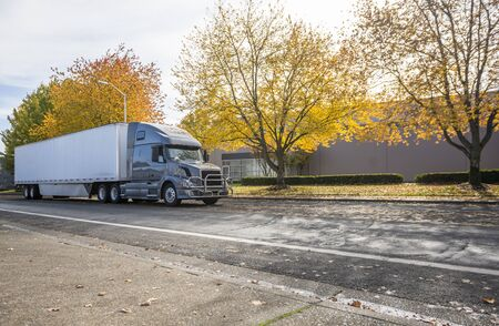Stylish big rig gray semi truck with grille guard and dry van semi trailer with spoiler skirt on the bottom standing on the autumn road with yellow trees at industrial area waiting for unloading Stock Photo