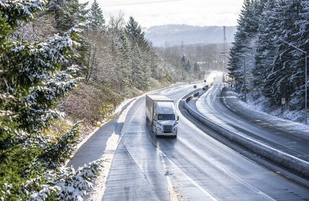 White modern bonnet popular professional big rig semi truck with dry van semi trailer going on the wet dangerous slippery icy winter road with snow on the trees on the sides of the divided highway Stok Fotoğraf