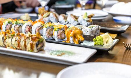 Plates with various kinds of expertly cooked and sliced sushi with spices and hot sauces are displayed on dining table to enjoy delicious and dietary natural foods containing seafood and organic rice