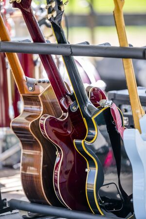 Different acoustic and electric guitars stand on a special stand on the stage to provide musicians with the opportunity to demonstrate to their listeners full range of their creative achievements Imagens