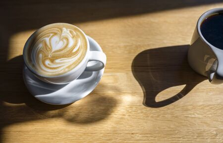 A cup of fragrant fresh coffee with a pattern on thick foam stands on a table lit by the sun, waiting for those who want to enjoy this delicious invigorating drink, raising vitality to a new level