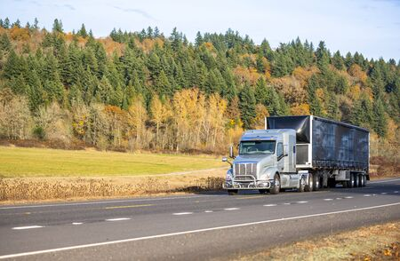 Big rig bonnet American low cab semi truck with pipe grille guard and sleeping compartment transporting cargo in black covered semi trailer with frame moving on the road with autumn trees and meadow Imagens