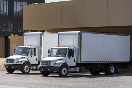Petits semi-camions professionnels compacts de qualité industrielle avec de longues remorques à caisse debout dans un quai d'entrepôt chargeant différentes cargaisons pour la prochaine livraison rapide Banque d'images