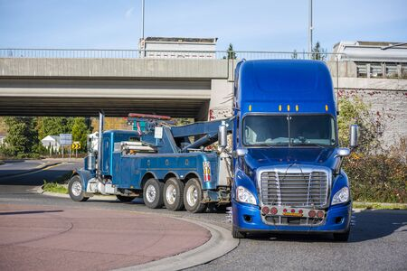 Mobile big rig tow truck with lifting boom and three driving truck rear axles towing broken blue big rig semi truck tractor with emergency lights on the grill going under the bridge to repair shop Stockfoto