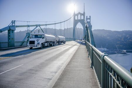 Big rig day cab for local deliveries white semi truck transporting liquid cargo in two tank semi trailers driving on the arched gothic St Johns Bridge in Portland industrial area with sunshine