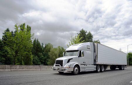 Bonnet Big Rig Langstrecken-Sattelzug mit Rohrgitterschutz, der kommerzielle Fracht im Kühlschrank-Sattelzug transportiert, der auf der breiten Autobahn mit Bäumen und Wolken im Hintergrund läuft