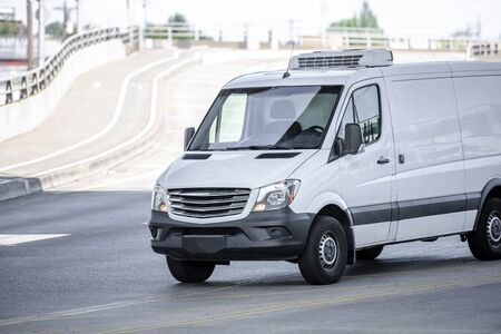 Comfortable compact white commercial cargo mini van for local deliveries and carry small business driving on the road on green metal truss bridge