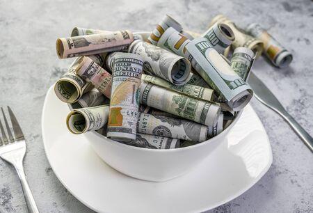 Billets en espèces de billets en dollars américains de diverses valeurs faciales comme métaphore du travail acharné et de la prospérité à la suite d'un travail réussi qui a permis à une personne de fournir à sa vie l'argent nécessaire
