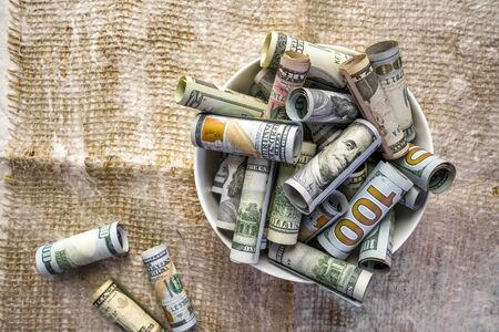 Cash banknotes of American dollar bills of various values stand on the table as a metaphor for eating up life values and a reminder of the frailty of money in exchange for a full-fledged life