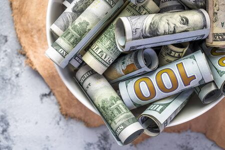 Cash banknotes of American dollar bills of various face values as a metaphor for hard work and prosperity as a result of successful work ennobling a person in providing his life with necessary money