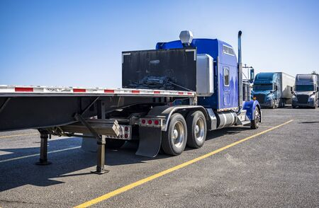 Big rig long haul blue semi truck with empty flat bed semi trailer standing on truck stop parking lot opposite another semi trucks standing in row for truck drivers rest according to schedule Stock Photo