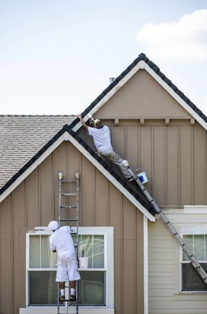 Painter man in white clothes with a protective scarf on his head paints a wooden window trim with a brush while standing on a high ladder leaning against the facade of a residential building