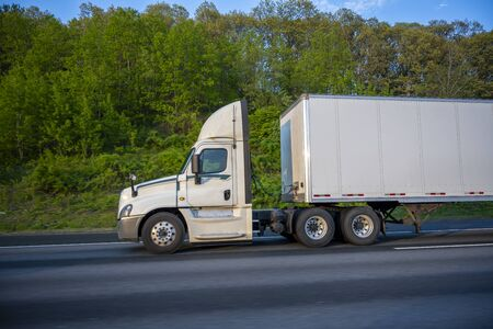 White Big rig day cab semi truck with roof spoiler for better aerodynamics and air resistance improvements transporting cargo in dry van semi trailer running on the road with green trees on the side Imagens
