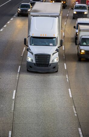Big rig white industrial long haul bonnet semi truck with black grille transporting commercial cargo in semi trailer running on evening wide highway with another traffic cars Stock Photo