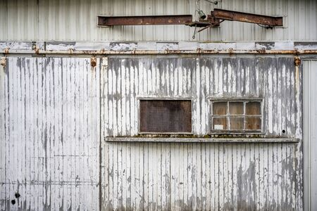 Windows closed by a piece of plywood on the on sliding roller wooden gate sheathed with slats with peeling paint wall of an old industrial warehouse building