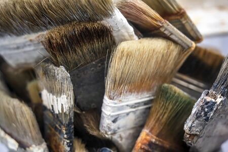 Various art brushes of different thicknesses and shapes for working with oil or acrylic paint stand