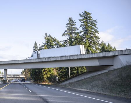 Big rig classic bonnet diesel long haul semi truck with dry van semi trailer transporting cargo and running on the overpass road across the straight divided highway road with trees on the side