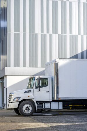 Medium duty day cab rig compact white industrial semi truck with box trailer for local deliveries standing on the building parking lot for unloading delivered goods on the urban city street