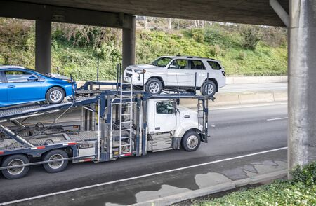 Powerful big rig diesel industrial grade professional car hauler semi truck transporting cars on the two level hydraulic semi trailer running under the concrete bridge across the wide highway road 写真素材