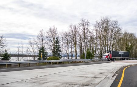 Red classic big rig semi truck with covered black semi trailer turning on the circle road ontersection along the Columbia River.jpg