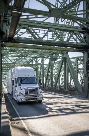 Big rig powerful industrial long haul white diesel semi truck with grille guard transporting commercial cargo in dry van semi trailer driving on the truss bascule Columbia River Interstate Bridge