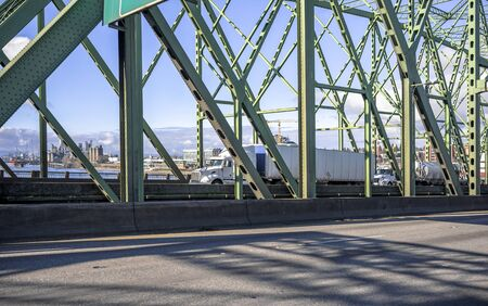 Convoy of different big rigs industrial long haul white diesel semi trucks transporting commercial cargo in dry van and tank semi trailers driving on the bascule Columbia River Interstate Bridge