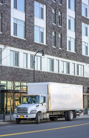 Medium duty day cab rig compact white industrial semi truck with box trailer for local deliveries standing on the urban city street with multilevel modern bricks apartments building 写真素材